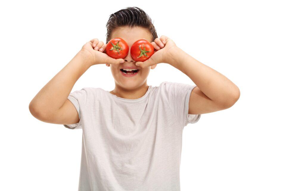 Kind mit Tomaten auf den Augen
